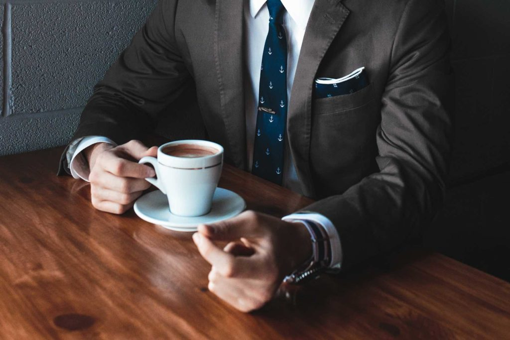 Photo of businessman holding cup of coffee.